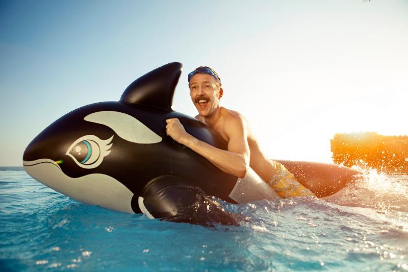 Homem brincando na piscina com baleia inflável